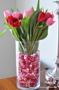 This would be so easy to do. A quick trip to the store for Valentine's Day M & M's, a large vase and flowers you like.  I think the tulips are great.  I would caution you, put a small container in the larger vase and fill with water. Then pour candy around the small container. Place the flowers in the container with water.  That way the flowers stay fresh and the candy stays dry. The florist would charge you $$$ for this.