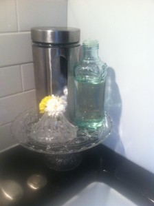 Am idea I stole from Pinterest. I use a inexpensive cake plate to hold kitchen supplies and some fresh cuttings.